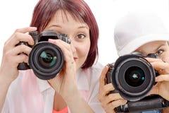 2 красивых молодой женщины используя камеру стоковая фотография