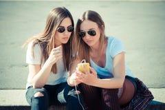 2 красивых молодой женщины используя умный телефон Стоковое Изображение RF