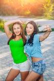 2 красивых молодой женщины используя умный телефон Стоковые Фото