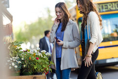 2 красивых молодой женщины идя и говоря в улице Стоковые Изображения