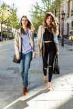 2 красивых молодой женщины идя и говоря в улице Стоковые Фото