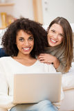2 красивых молодой женщины ослабляя на софе Стоковые Фото