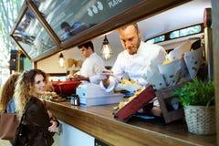 2 красивых молодой женщины покупая картошки барбекю на тележке еды Стоковые Фотографии RF