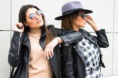 2 красивых молодой женщины представляя в городке модно и стильные стоковые фотографии rf