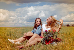 2 красивых молодой женщины сидя на луге лета Стоковая Фотография RF