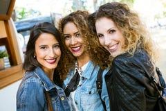 3 красивых молодой женщины смотря камеру в улице Стоковое Изображение