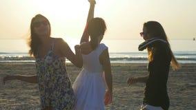 3 красивых молодой женщины танцуя на пляже на восходе солнца сток-видео