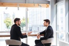 2 красивых молодых бизнесмена говоря в офисе Стоковые Изображения RF