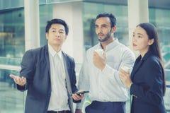 2 красивых молодых бизнесмена и дама в классических костюмах говорят Стоковые Фото