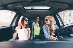 3 красивых молодых жизнерадостных женщины держа хозяйственные сумки и смотря один другого с улыбкой пока сидящ в автомобиле Стоковое фото RF