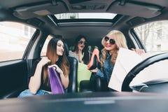 3 красивых молодых жизнерадостных женщины держа хозяйственные сумки и смотря один другого с улыбкой пока сидящ в автомобиле Стоковое Изображение