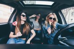 3 красивых молодых жизнерадостных женщины смотря один другого с улыбкой и есть леденцы на палочке пока сидящ в автомобиле Стоковые Фото
