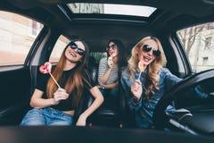 4 красивых молодых жизнерадостных женщины смотря один другого с улыбкой и едят леденцы на палочке пока сидящ в автомобиле Стоковое Фото