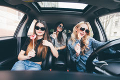 4 красивых молодых жизнерадостных женщины смотря один другого с улыбкой и едят леденцы на палочке пока сидящ в автомобиле Стоковые Изображения RF