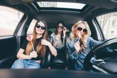 4 красивых молодых жизнерадостных женщины смотря один другого с улыбкой и едят леденцы на палочке пока сидящ в автомобиле Стоковое фото RF