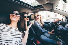4 красивых молодых жизнерадостных женщины смотря один другого с улыбкой пока сидящ в автомобиле Стоковое Изображение RF
