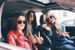 4 красивых молодых жизнерадостных женщины смотря один другого с улыбкой пока сидящ в автомобиле Стоковые Фотографии RF