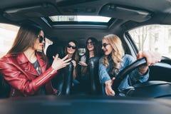 4 красивых молодых жизнерадостных женщины смотря счастливый и шаловливый пока сидящ в автомобиле Стоковые Фото