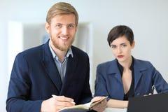 2 красивых молодых предпринимателя сидя в офисе и усмехаться Стоковые Изображения