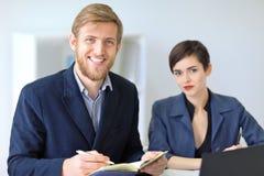 2 красивых молодых предпринимателя сидя в офисе и усмехаться Стоковая Фотография