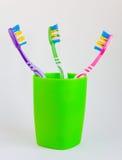 3 красивых пестротканых зубной щетки стоят в зеленые glas Стоковое Изображение