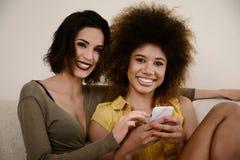 2 красивых подруги сплетни принимая selfie с smartphone Стоковое Фото