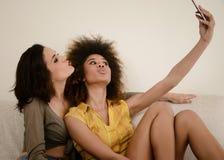 2 красивых подруги сплетни принимая selfie с smartphone Стоковые Фотографии RF