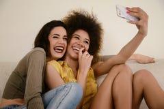2 красивых подруги сплетни принимая selfie с smartphone Стоковая Фотография