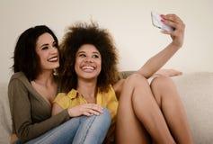 2 красивых подруги сплетни принимая selfie с smartphone Стоковые Фото
