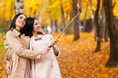 2 красивых подруги делают selfie на листьях осени предпосылки Стоковые Фотографии RF