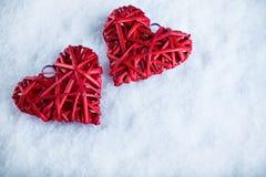 2 красивых романтичных винтажных красных сердца совместно на белой предпосылке зимы снега Влюбленность и концепция дня валентинок Стоковые Изображения