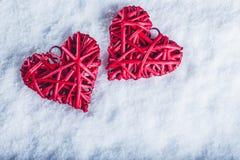 2 красивых романтичных винтажных красных сердца совместно на белой предпосылке снега Влюбленность и концепция дня валентинок St Стоковая Фотография