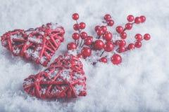 2 красивых романтичных винтажных красных сердца с ягодами омелы на белом снеге Рождество, влюбленность и концепция дня валентинок Стоковое Изображение