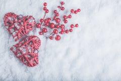 2 красивых романтичных винтажных красных сердца с ягодами омелы на белом снеге Рождество, влюбленность и концепция дня валентинок Стоковые Фото