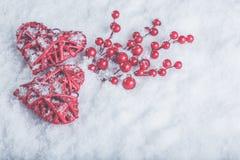 2 красивых романтичных винтажных красных сердца с ягодами омелы на белом снеге Рождество, влюбленность и концепция дня валентинок Стоковая Фотография