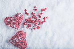 2 красивых романтичных винтажных красных сердца с ягодами омелы на белом снеге Рождество, влюбленность и концепция дня валентинок Стоковое Фото