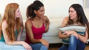 3 красивых друз беседуя пока сидящ на кресле сток-видео