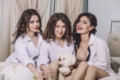 3 красивых друз молодых женщин беседуя в спальне внутри Стоковое фото RF