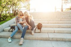 2 красивых студента наблюдая содержание средств массовой информации на линии в умном телефоне в парке Стоковые Фото