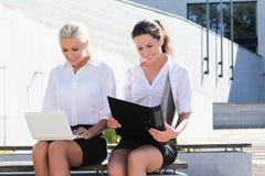 2 красивых студента сидя с компьтер-книжкой над backgroun улицы Стоковая Фотография