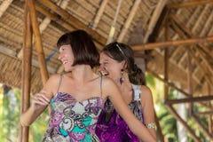 2 красивых счастливых маленькой девочки сидя в деревянном газебо на солнечном дне и имеющ потеху, усмехаться и смеяться над тропи Стоковое Изображение