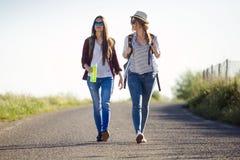 2 красивых hikers дам идя на дорогу Стоковая Фотография RF