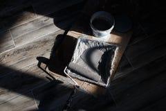 Красить стены комнаты Поднос с роликом краски и краской в свете солнца падая через окна стоковые фото