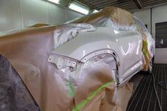 Красить части тела автомобиля двери и белого крыла водителя в будочке брызг в ремонтной мастерской тела; другие элементы ar стоковая фотография