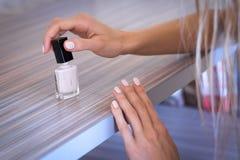 Красит ее ногти с белой краской Стоковые Изображения