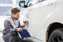 Краска автомобиля мужского работника ремонта рассматривая с оборудованием в ремонтной мастерской Стоковые Фото