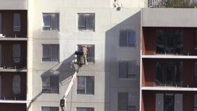 Краска брызга человека работника термальная белая на плоской стене дома сток-видео