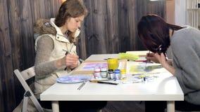 Краска 2 взрослых женщин с покрашенными акрилами в художественном училище