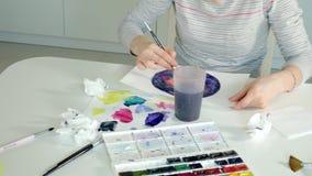 Краска взрослых женщин с покрашенными красками акварели в домашней студии