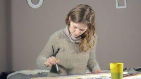 Краска взрослых женщин с покрашенными красками акварели в художественном училище